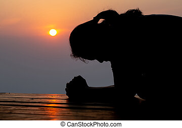 Silhouette of woman praying in the morning