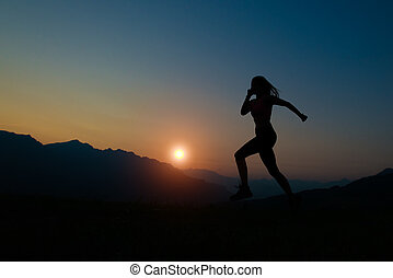 Silhouette of woman running at sunset in the mountains