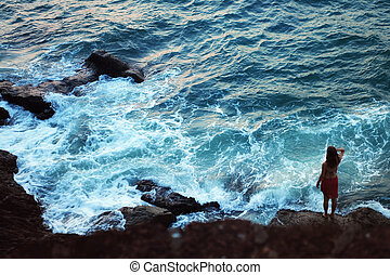 Silhouette of woman standing on a rock face
