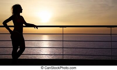 silhouette of woman standing on deck of cruise ship