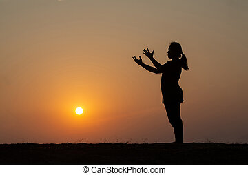 Silhouette of woman standing with arms raised on mountain