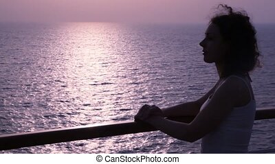 silhouette of woman stands on deck of cruise ship