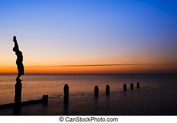 Silhouette of woman stretching doing yoga on groynes on beach