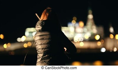 Silhouette of woman violinist playing on violin at night city in cold season