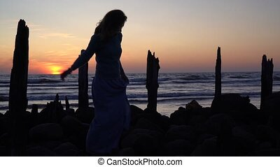 Silhouette of woman wearing dress walking through old pier stones on beautiful sunset background. Camera movement follow shot with gimbal.