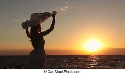 Silhouette of woman with scarf on beach at sunset -...