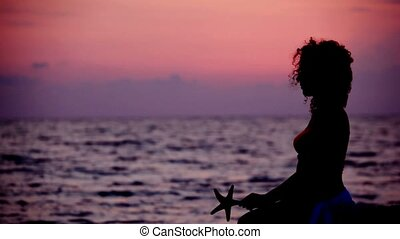 silhouette of woman with sea star in hands on beach, sunset sky in background