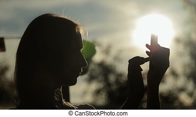 silhouette of woman with smart phone at sunset
