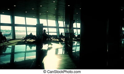 Silhouette of woman with suitcase walking through hall at airport, slow motion, sun shining