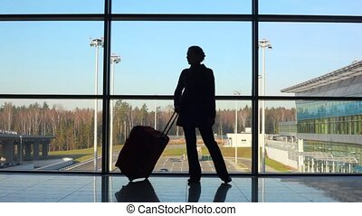 silhouette of woman with travel luggage stands against window