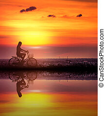 Silhouette of Women biking bicycle on the river side.