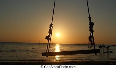 Silhouette of wooden swing seat hanging on coconut tree by...