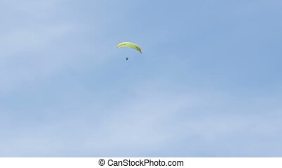 Silhouette of yellow paraglider flying against the sky -...