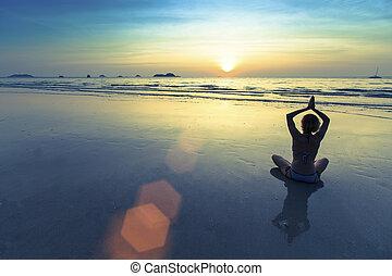 Silhouette of yoga woman meditating on the ocean beach.