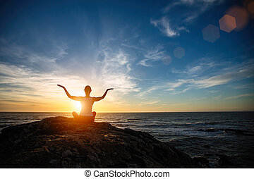 Silhouette of yoga woman sitting in Lotus position on the beach during amazing sunset.