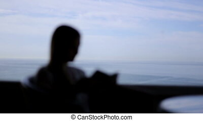 silhouette of young beautiful girl sits in a cafe with panoramic views of atlantic ocean. Morning with a book, notepad, reading, thinking