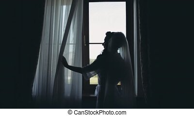 Silhouette of young bride drinks coffee in morning in front of window. Woman with veil getting ready to wedding ceremony