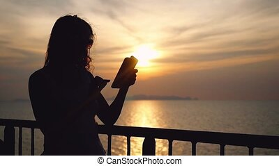 Silhouette of young brunette woman in sunglasses standing on deck of cruise ship and using her smart phone. Wind waving her hair. slow motion.