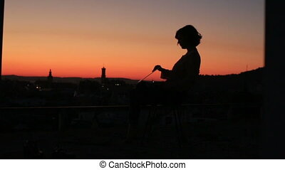 Silhouette of young businees woman using her laptop on the sunset background in the city landscape