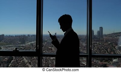 Silhouette of young businessman in office is browsing phone near the window with panoramic city view.