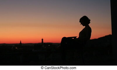 Silhouette of young charming businees woman using her laptop on the sunset background in the city landscape