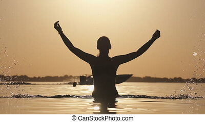 Silhouette of Young Cheerful Woman Splashing River Water at Sunset. Slow Motion