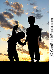 Silhouette of Young Children Holding Hands at Sunset