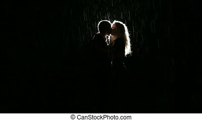 Silhouette of young couple ardently kissing in the dark...
