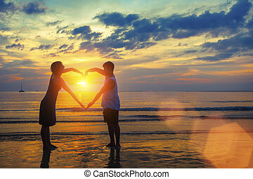 Silhouette of young couple holding hands in heart shape on the ocean beach during sunset.
