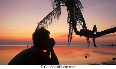 Silhouette of young couple on the beach. Man takes a picture his girlfriend while girl lies on a palm tree during amazing sunset. slwo motion. People enjoying vacations concept