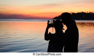 Silhouette of young couple on the beach take a selfie portrait at sunset. Slow motion. People enjoying vacations concept.