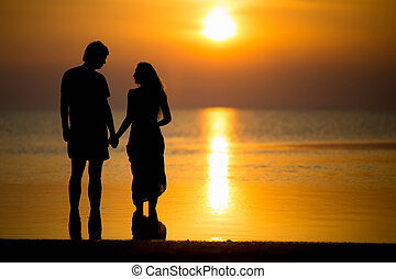 Silhouette of young couple posing on the beach at sunset