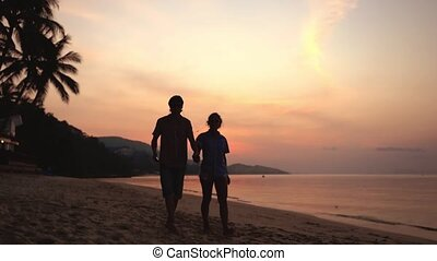 Silhouette of young couple walks on the beach listen to...
