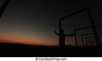 Silhouette of young dreamy girl jumping and having fun on the city bridge and raising her hands up. Sunset background