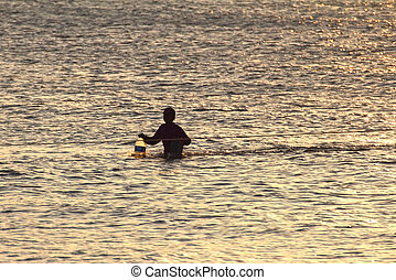 Silhouette of young fisherman in ocean at sunset
