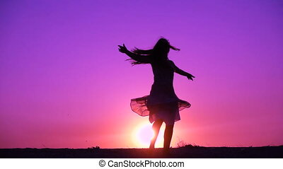 Silhouette of young girl dancing against sunset