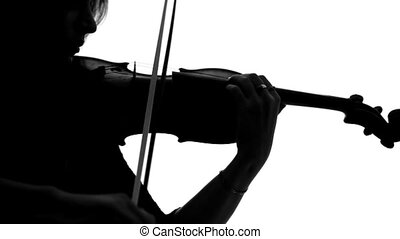 Silhouette of young girl in a dress playing the violin