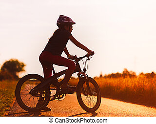 Silhouette of young girl on a bicycle at sunset