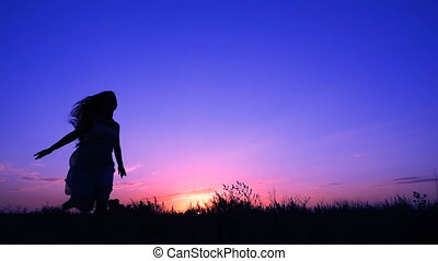 Silhouette of young girl running against pink sky