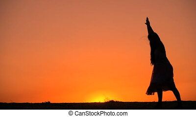 Silhouette of young girl standing somersault against sunset,...