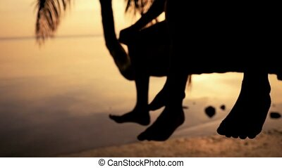 Silhouette of young happy father with his daughter sit on a palm tree. Having fun on summer happy family vacation. slow motion. 1920x1080, hd