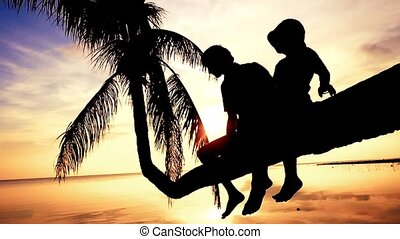 Silhouette of young happy father with his daughter sit on a palm tree during beautiful bright sunset. Having fun on summer happy family vacation. slow motion. 1920x1080, hd