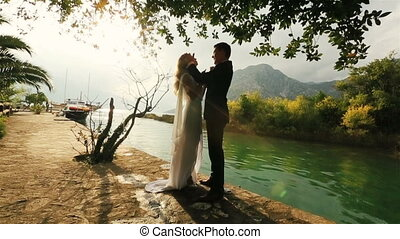 Silhouette of Young happy wedding couplehugging on the old quay in Montenegro, Budva with sea and mountains on background