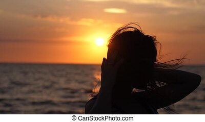 Silhouette of young happy woman have fun listening music in headphones on the beach at amazing sunset in slow motion.