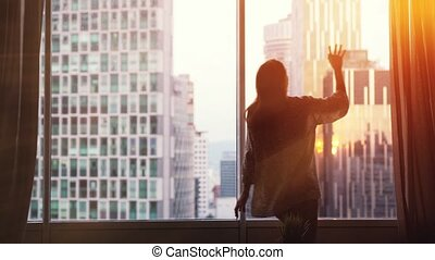 Silhouette of young joyful woman runs and opens curtains on...