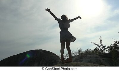 Silhouette of young joyful woman standing on the rock rises...