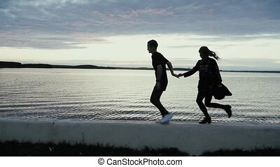 young man and girl running along the embankment at sunset, slow motion