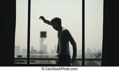 Silhouette of young man dancing ad listening music in...