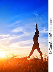 Silhouette of young man doing yoga on the meadow at sunset in the countryside.