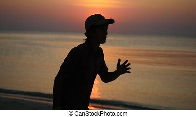 Silhouette of young man jogging on beach during sunset, slow motion.